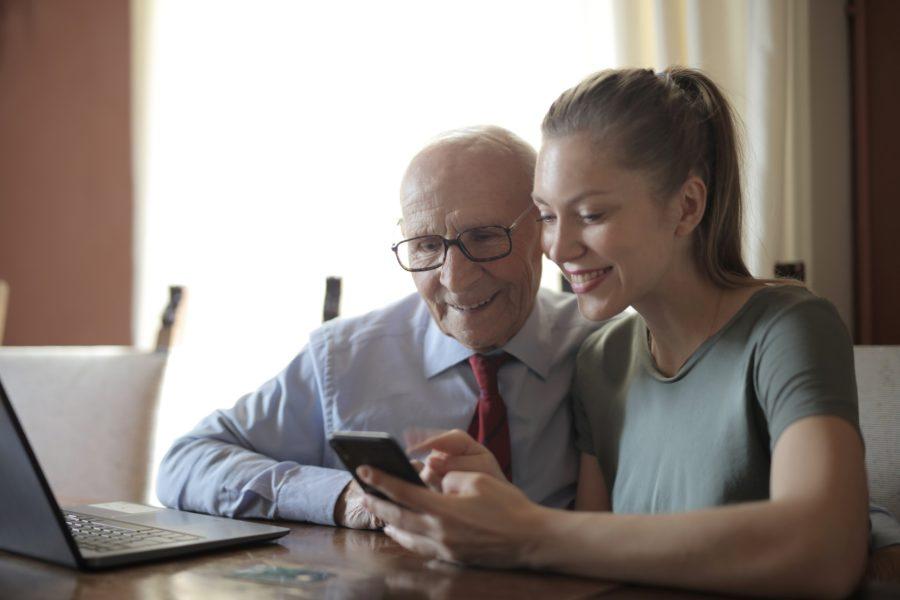 Junge Frau zeigt älteren Herrn etwas auf dem Smartphone